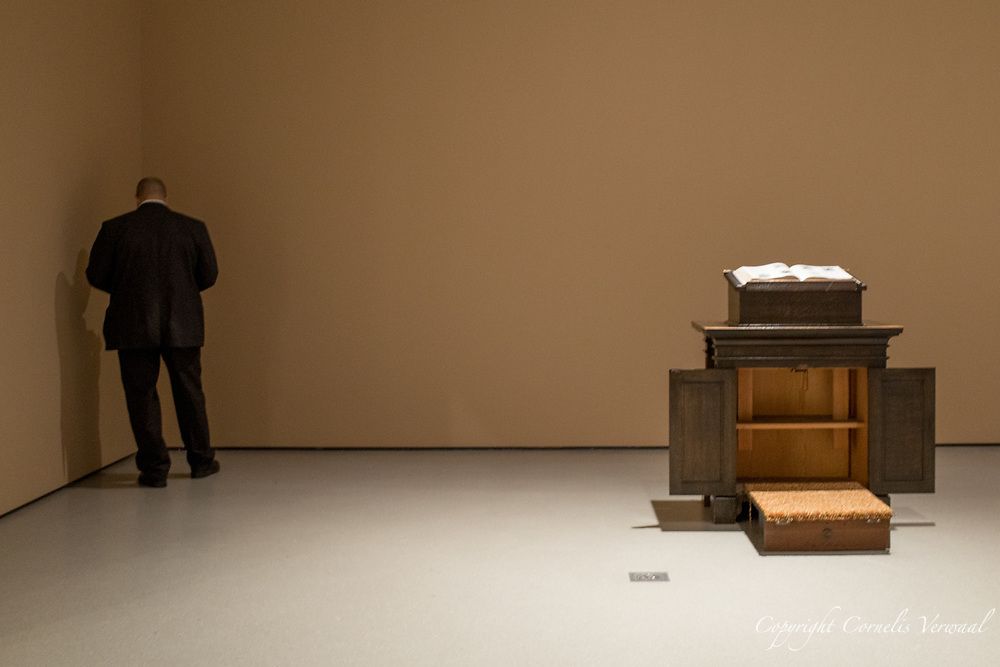 """MoMA guard secretly texting next to <br /> David Hammons installation of """"The Hole Bible: Old Testament"""""""