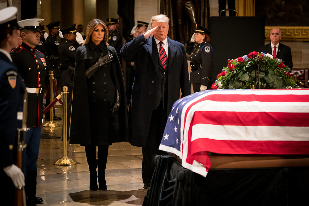 """First Lady Melania Trump and President Donald Trump salute the casket of Former President George H.W. Bush as it lies in state at the U.S. Capitol on Dec. 3, 2018. Trump has had a frosty relationship with the Bush family. He called his 2016 GOP primary opponent Jeb Bush """"low energy,"""" criticized the leadership of President George W. Bush and recently mocked the elder Bush's """"thousand points of light"""" volunteer program. President Trump still praised George H.W. Bush on Twitter as someone who """"led a long, successful and beautiful life."""""""