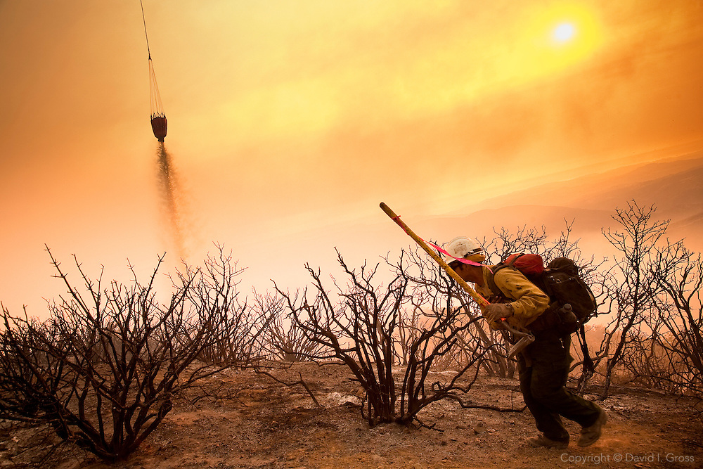A helicopter drops water to cool a spot fire so Forest Service Hotshots can put it out by hand.