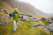 Liana Welty hikes the rocky coast of Vaeroy Island, Lofoten Islands, Norway.