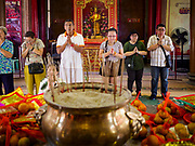 29 JANUARY 2019 - BANGKOK, THAILAND:       People pray in front of an altar of New Year's offerings at Wat Mangon Kamalawat, a large Chinese Buddhist temple in Bangkok's Chinatown district. Chinese New Year celebrations in Bangkok start on February 4, 2019. The coming year will be the Year of the Pig in the Chinese zodiac. About 14% of Thais are of Chinese ancestry and Lunar New Year, also called Chinese New Year or Tet is widely celebrated in Chinese communities in Thailand.        PHOTO BY JACK KURTZ