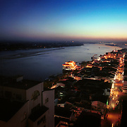 Dandong city, China and Sinuiju City, North Korea, 11-2003..A night scene of China's gleaming Dandong city (right) and North Korea's Sinuiju city (left). When the sun sets, North Korea plunges into darkness due to eletricty shortage. ..Ruled by the messianic leader Kim Il Sung and his son Kim Jong Il since 1948, North Korea has stubbornly stuck to its juche (self-reliance) ideology and siege mentality, imposing one Stalinist economic plan after another. Floods, droughts and mismanagement in the 1990s plunged the country into a preventable famine, killing up to three million, or 13 percent of the population. It now depends heavily on Chinese aid...