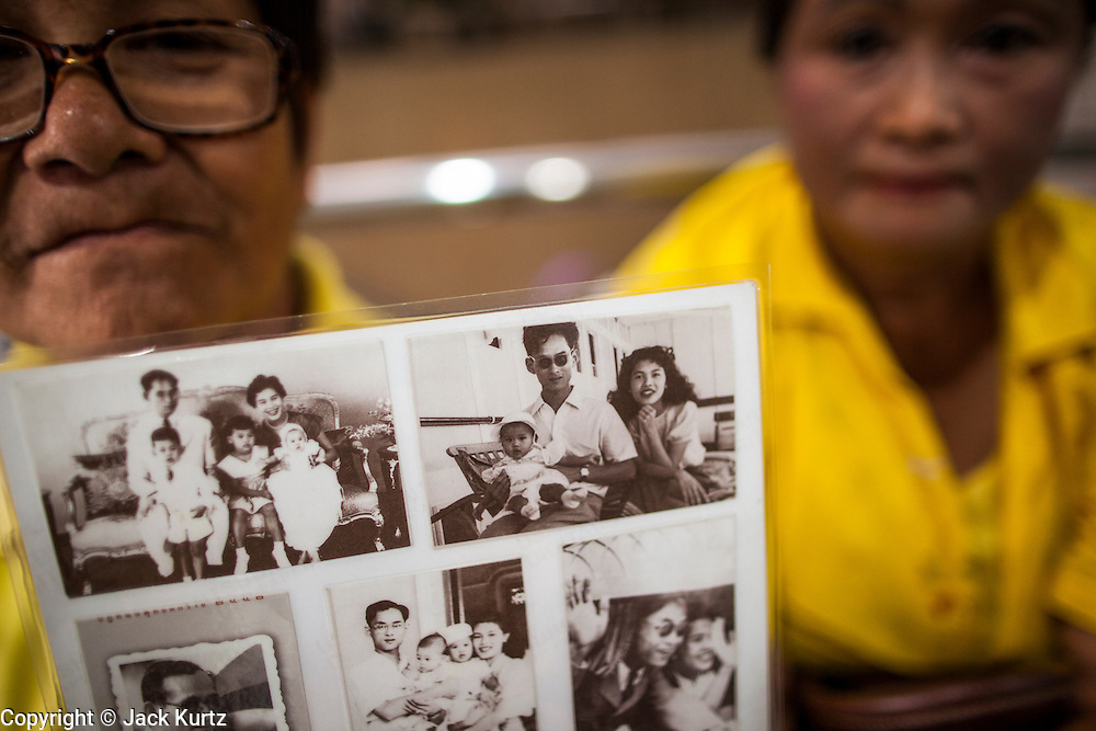 04 DECEMBER 2012 - BANGKOK, THAILAND: A woman dressed in yellow holds up family pictures of Bhumibol Adulyadej, the King of Thailand, while she waits for him in the lobby of Siriraj Hospital. People pack the lobby of the hospital hoping the catch a glimpse of the King if he should make an unexpected visit to the lobby. Yellow is the official color of the Thai King, who celebrates his 85th birthday Wednesday, Dec. 5. The King lives in Siriraj. He is expected to make a rare public appearance and address the nation from Mukkhadej balcony of the Ananta Samakhom Throne Hall in the Royal Plaza. The last time he did so was in 2006. His birthday is a public holiday in Thailand and hundreds of thousands of people are expected to jam the streets around the Royal Plaza and Grand Palace to participate in the festivities.    PHOTO BY JACK KURTZ