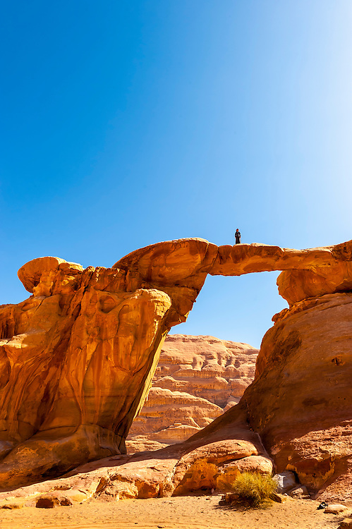 Bedouin boy atop the Burdah Rock Bridge, Arabian Desert, Wadi Rum, Jordan.