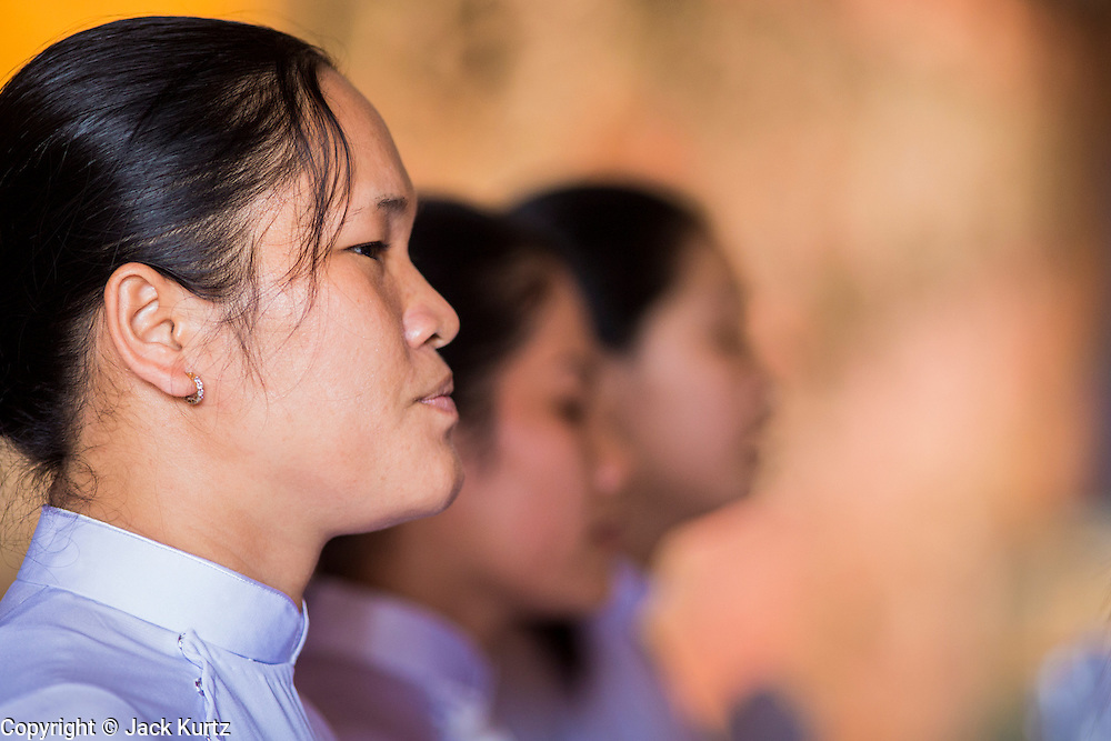 """29 MARCH 2012 - TAY NINH, VIETNAM:  A woman prays during noon services at the Cao Dai Holy See in Tay Ninh, Vietnam. Cao Dai (also Caodaiism) is a syncretistic, monotheistic religion, officially established in the city of Tây Ninh, southern Vietnam in 1926. Cao means """"high"""" and """"Dai"""" means """"dais"""" (as in a platform or altar raised above the surrounding level to give prominence to the person on it). Estimates of Cao Dai adherents in Vietnam vary, but most sources give two to three million, but there may be up to six million. An additional 30,000 Vietnamese exiles, in the United States, Europe, and Australia are Cao Dai followers. During the Vietnam's wars from 1945-1975, members of Cao Dai were active in political and military struggles, both against French colonial forces and Prime Minister Ngo Dinh Diem of South Vietnam. Their opposition to the communist forces until 1975 was a factor in their repression after the fall of Saigon in 1975, when the incoming communist government proscribed the practice of Cao Dai. In 1997, the Cao Dai was granted legal recognition. Cao Dai's pantheon of saints includes such diverse figures as the Buddha, Confucius, Jesus Christ, Muhammad, Pericles, Julius Caesar, Joan of Arc, Victor Hugo, and the Chinese revolutionary leader Sun Yat-sen. These are honored at Cao Dai temples, along with ancestors.     PHOTO BY JACK KURTZ"""