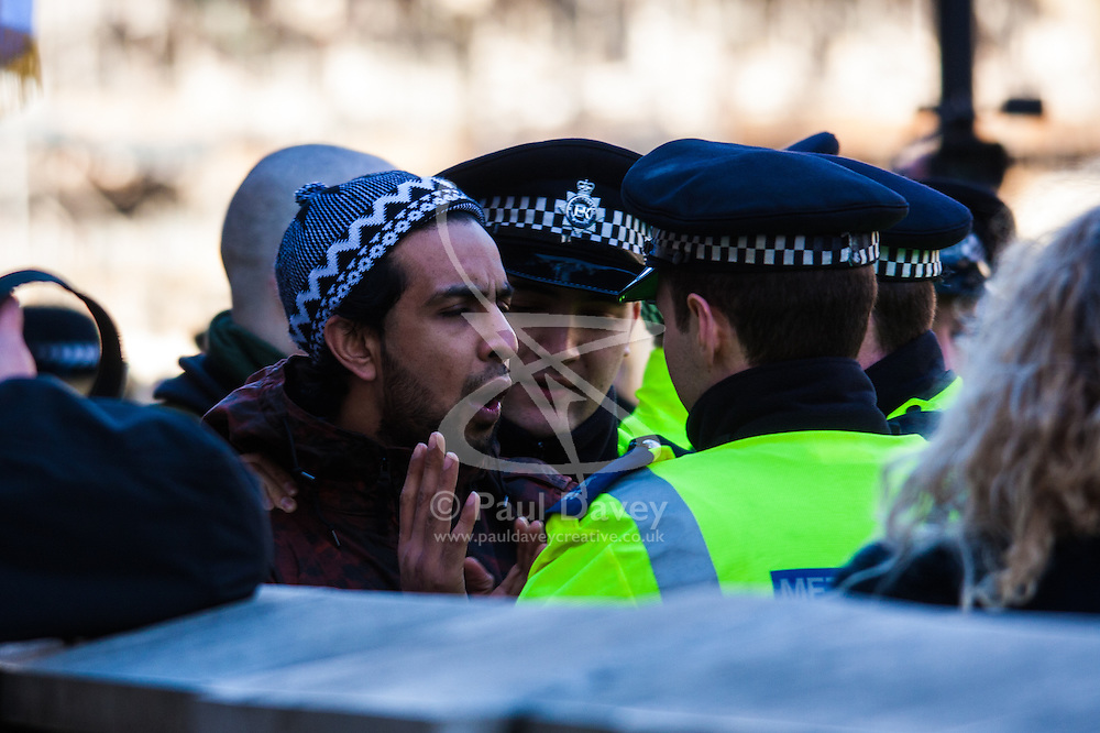 London, February 8th 2015. Muslims demonstrate outside Downing Street  to denounce the uncivilised expressionists reprinting of the cartoon image of the Holy Prophet Muhammad. PICTURED: Police intervene as a young Muslim protester gets hot under the collar with far right Britain First counter-demonstrators.