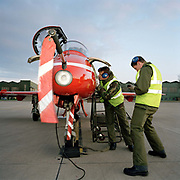 Engineering ground staff of the Red Arrows, Britain's RAF aerobatic team, during turnarounds of training flights. Wearing ear-defenders, military green overalls and fluorescent tabard, a 'line' engineer from the elite 'Red Arrows', Britain's prestigious Royal Air Force aerobatic team, inspect the avionics of a Hawk aircraft immediately after a winter training flight at the team's headquarters at a damp RAF Scampton, Lincolnshire. The men are members of the team's support ground crew (called the Blues because of their distinctive blue overalls worn at summer air shows). The team's support ground crew who outnumber the pilots 8:1 and without them, the Red Arrows couldn't fly. Eleven trades are imported from some sixty that the RAF employs and teaches.