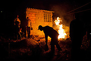 A man picks up a bucket in front of a fire at night. Isidoro occupation in Belo Horizonte, Minas Gerais in a large  amount of land that was occupied by the MLB, a Brazilian workers social movement, it faced eviction in July / August 2014. (photo by Phil Clarke Hill/In Pictures via Getty Images)