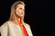 A beige jacket with tan leather shoulders and collar, worn over a tangerine blouse. By Monika Chiang at Spring 2013 Fashion Week in New York.