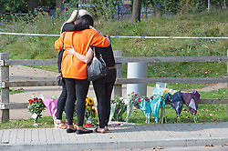 © Licensed to London News Pictures 21/09/2021. <br /> Kidbrooke, UK, Friends hug after laying flowers at the scene. A large police cordon is still in place around Cator Park at Kidbrooke Village in Kidbrooke, South East London today after the body of 28 year old school teacher Sabina Nessa was found near a community centre. Police believe Sabina was murdered by a stranger. Photo credit:Grant Falvey/LNP