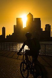 © Licensed to London News Pictures. 05/10/2016. LONDON, UK.  A cyclist on the River Thames path as the sun rises behind Canary Wharf and London's financial district this morning. Forecasters are predicting a day of clear and sunny weather in London today.  Photo credit: Vickie Flores/LNP