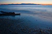 Sunset at Golden Gardens beach in Seattle, Washington. The Olympic Mountains are visible in the distance.