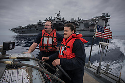 PACIFIC OCEAN (May 10, 2017) Boatswain's Mate 1st Class Ryan Myers, left, instructs Seaman Nicole Swick during search and rescue operations as they pass the aircraft carrier USS Theodore Roosevelt (CVN 71). Theodore Roosevelt is participating in a group sail training unit exercise to enhance mission-readiness and warfighting capabilities between the ships, air wing and staffs through simulated real-world scenarios. (U.S. Navy photo by Mass Communication Specialist 3rd Class Spencer Roberts/Released) 170510-N-MJ135-0104 <br /> Join the conversation:<br /> http://www.navy.mil/viewGallery.asp<br /> http://www.facebook.com/USNavy<br /> http://www.twitter.com/USNavy<br /> http://navylive.dodlive.mil<br /> http://pinterest.com<br /> https://plus.google.com