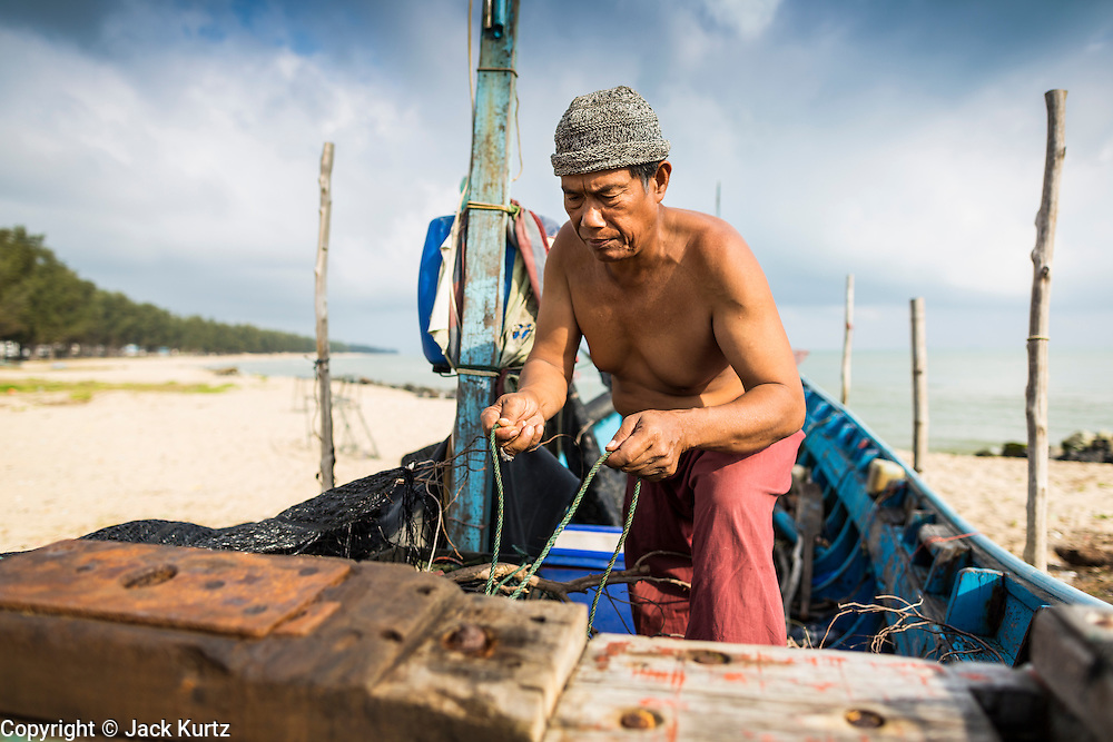 07 FEBRUARY 2014 - KAO SENG, SONGKHLA, THAILAND:  A fisherman readies his boat before putting it in the water in Kao Seng. Kao Seng is a traditional Muslim fishing village on the Gulf of Siam near the town of Songkhla, in the province of Songkhla. In general, their boats go about 4AM and come back in about 9AM. Sometimes the small boats are kept in port because of heavy seas or bad storms.     PHOTO BY JACK KURTZ