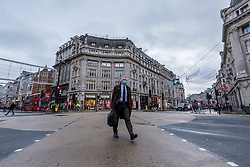© Licensed to London News Pictures. 21/12/2020. LONDON, UK. A man in a suit wearing a facemask crosses Oxford Circus in the West End as Tier 4, Stay at Home, alert level restrictions are imposed on much of the UK to combat the ongoing coronavirus pandemic in the light of a recently discovered mutant strain that was discovered in the south east of England.  Photo credit: Stephen Chung/LNP
