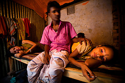 Sex worker sisters Nodi,14, right, and Shetu, 17, left, lie down by a customer at brothel in Tangail, Bangladesh. Nodi run away from home after falling in love with a Hindu boy and ended up in the brothel with her sister. Shetu was sold to a brothel with a false job offer after she run away from an abusive husband.<br /> The majority of the 20,000 to 30,000 female sex workers in Bangladesh are victims of trafficking.