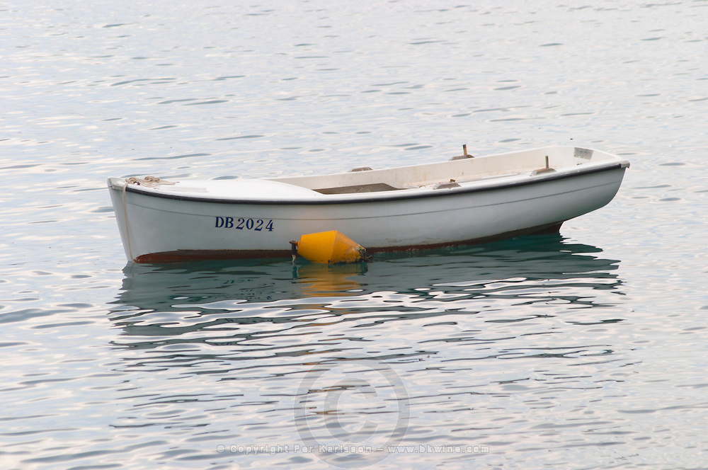 A white rowing boat moored by a yellow buoy Uvala Sumartin bay between Babin Kuk and Lapad peninsulas. Dubrovnik, new city. Dalmatian Coast, Croatia, Europe.