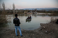 A Syrian man waits for a relative to cross the Orontes river into Turkey, from Syria on the far bank. Hacipasa, Turkey. February 27th 2013
