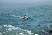 Kayaker riding surfing wave near Fort Point and Golden Gate Bridge, San Francisco, California, USA
