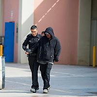 091313        Brian Leddy<br /> Community Service Aid Justin Benally escorts a man to a transport vehicle Friday, Sept. 13.