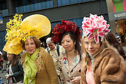 Three women wearing elaborate floral hats by New York's milliner, TheTipsy Topper.