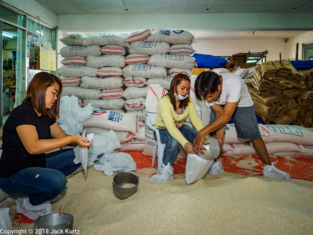"""22 JANUARY 2018 - LEGAZPI, ALBAY, PHILIPPINES:  JANE BLANCA, left, ANN BACEA, and WANY MATEBUENA, employees of the Albay Provincial Social Welfare and Development Office package emergency food supplies to be delivered to the evacuees from the Mayon volcano eruptions. There were a series of eruptions on the Mayon volcano near Legazpi Monday. The eruptions started Sunday night and continued through the day. At about midday the volcano sent a plume of ash and smoke towering over Camalig, the largest municipality near the volcano. The Philippine Institute of Volcanology and Seismology (PHIVOLCS) extended the six kilometer danger zone to eight kilometers and raised the alert level from three to four. This is the first time the alert level has been at four since 2009. A level four alert means a """"Hazardous Eruption is Imminent"""" and there is """"intense unrest"""" in the volcano. The Mayon volcano is the most active volcano in the Philippines. Sunday and Monday's eruptions caused ash falls in several communities but there were no known injuries.   PHOTO BY JACK KURTZ"""