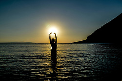 August 4, 2017 - Dafni, Messopion, Greece - A young female playing in the water standing in contrast to the sunset at Dafni, Messopion, Euboea on August 4., 2017. (Credit Image: © Wassilios Aswestopoulos/NurPhoto via ZUMA Press)