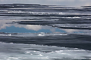 Sheets of ice and snow partially cover Yellowstone Lake. Reflection of clouds on the lake add to the mystery and imagination of this abstract capture.
