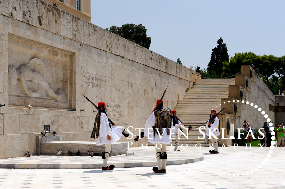 Syntagma square. Athens. Greece. View of Greek Evzones performing the very slow and highly stylized ceremonial changing of the guard at the monument to the Unknown Soldier in Athens. The monument to the Unknown Soldier, erected in 1929-1932, depicts a relief of a dying Greek solider and is watched around the clock by pairs of Evzones, elite members of the Presidential ceremonial guard unit, standing motionless outside their sentry boxes wearing traditional dress. These guards are wearing the full dress uniform consisting of a white, bell-sleeved shirt and a white foustanella with 400 pleats (Symbolising the 400 years of Ottoman occupation). It is only worn on Sundays or important national holidays.