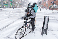 A London Deliveroo rider checking an address on his mobile phone in a snow storm.