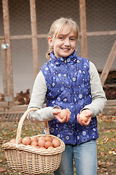 Blond girl holding basket with eggs on farm