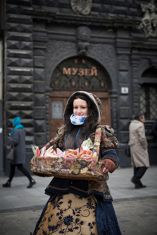 Olena, age 18, sells candy from a basket in Rynok Square in Lviv, Ukraine
