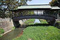 """The Sayabashi Bridge is a bridge over the Kanakura River in Kotohira, Kagawa Prefecture. This arched wooden bridge with copper roof in Kara-hafu style is said to have been constructed during the Genroku period(1688-1703).  It was named Sayabashi because its curved shape is similar to the scabbard of a sword. It is also known as the """"Uki Bashi or """"Floating Bridge"""" because it no legs. It was registered as a Registered Tangible Cultural Property in 1998."""