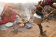 A woman prepares chapatties over an open fire in, Rajasthan, India.