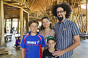"""Zach, is a teacher at Green School, he is pictured with his wife Sophie Daubisse and their two sons Milan is 12 years old, Sevan-Fidel is 9 years old, who are students at Green School. They are french residents<br /><br />The Green School (Bali) is one of a kind in Indonesia. It is a private, kindergarten to secondary International school located along the Ayung River near Ubud, Bali, Indonesia. The school buildings are of ecologically-sustainable design made primarily of bamboo, also using local grass and mud walls. There are over 600 students coming from over 40 countries with a percentage of scholarships for local Indonesian students.<br /><br />The impressive three-domed """"Heart of School Building"""" is 60 metres long and uses 2500 bamboo poles. The school also utilizes renewable building materials for some of its other needs, and almost everything, even the desks, chairs, some of the clothes and football goal posts are made of bamboo.<br /><br />The educational focus is on ecological sustainability. Subjects taught include English, mathematics and science, including ecology, the environment and sustainability, as well as the creative arts, global perspectives and environmental management. This educational establishment is unlike other international schools in Indonesia. <br /><br />Renewable energy sources, including solar power and hydroelectric vortex, provide over 50% of the energy needs of the school. The school has an organic permaculture system and prepares students to become stewards of the environment. <br /><br />The school was founded by John and Cynthia Hardy in 2008."""