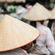 Women wearing a traditional Vietnamese conical hat at a food market in Hanoi, Vietnam.