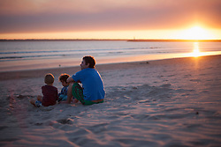 Father with two kids sitting on beach during sunset, Viana do Castelo, Norte Region, Portugal