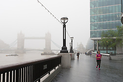 © Licensed to London News Pictures. 11/05/2016. LONDON, UK.  An early morning jogger runs along the Thames path, with Tower Bridge shrouded in fog during foggy and wet weather this morning.  Photo credit: Vickie Flores/LNP