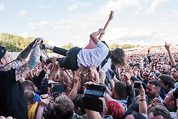 © Licensed to London News Pictures. 31/08/2019. Bristol, UK. Idles play the main stage at the Downs Festival. Idles' guitarist crowd surfs. Photo credit: Simon Chapman/LNP.
