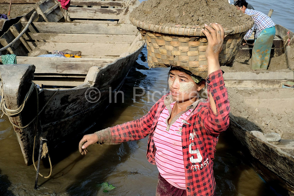 A woman labourer carrying a basket of sand from a boat on the Ayeyarwady river in Mandalay on 26th May 2016 in Myanmar