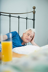 Portrait of mature man in bed with orange juice, smiling
