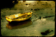 A small rowing boat moored on mud flats