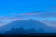 Early morning fog somewhat obscures the view of Mount Si at daybreak in Snoqualmie, Washington. Mount Si, which has an elevation of 4,167 feet (1,270 meters), is located at the western edge of the Cascade Range and is a remnant of an oceanic plate volcano. Its summit is a class 3 rock scramble known as the Haystack.
