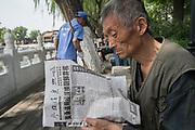 Old man reading newspaper, Gulou park, Beijing, China