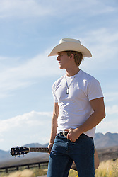 good looking cowboy walking on a rural road with a guitar