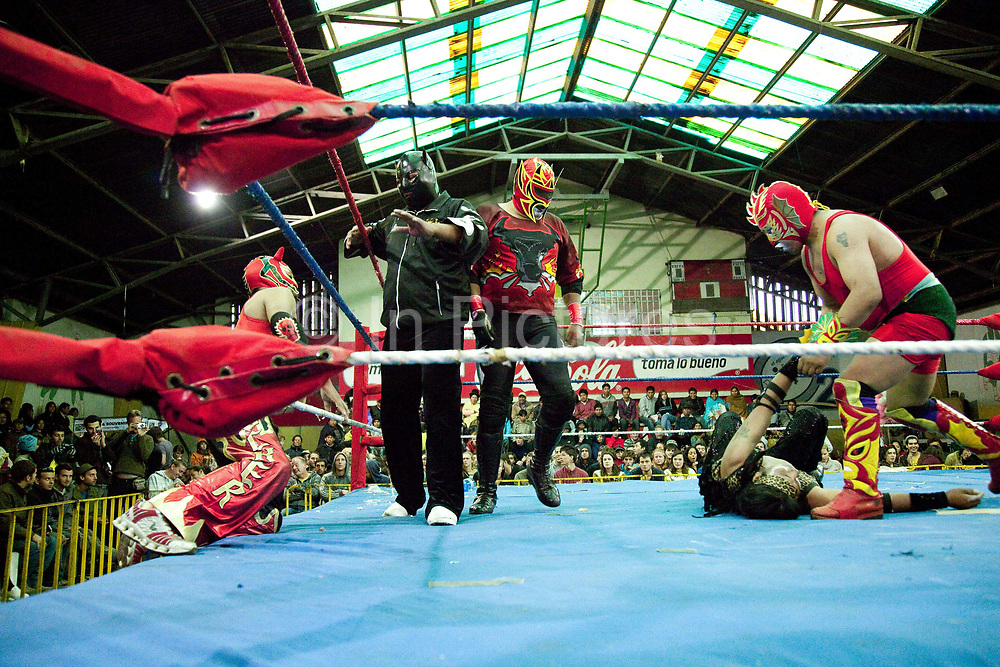 Several male wrestlers in ring fighting. Lucha Libre wrestling origniated in Mexico, but is popular in other latin Amercian countries, including in La Paz / El Alto, Bolivia. Male and female fighters participate in the theatrical staged fights to an adoring crowd of locals and foreigners alike.