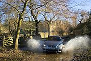 BMW 5 Series car drives through country lane ford, Swinbrook, Oxfordshire, United Kingdom