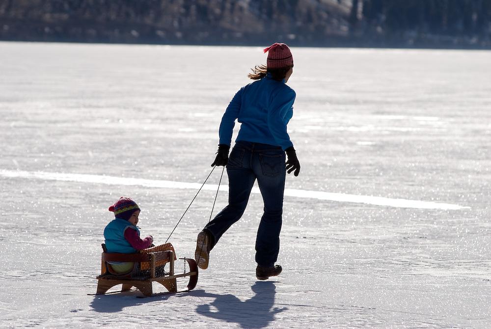 Pulling child in sled on Wallowa Lake, Oregon.