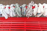 Display of women's scarves each scarf tied on brightly coloured bench in Lubeck, Northern Germany