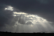 Crepuscular rays stream through clouds in Western Iceland